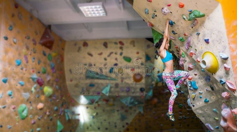 En kvinna utbildar för att klättra arkivbild