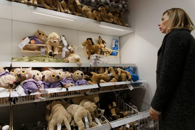 En kvinna väljer en mjuk leksak i paviljongen av det IKEA lagret royaltyfri foto