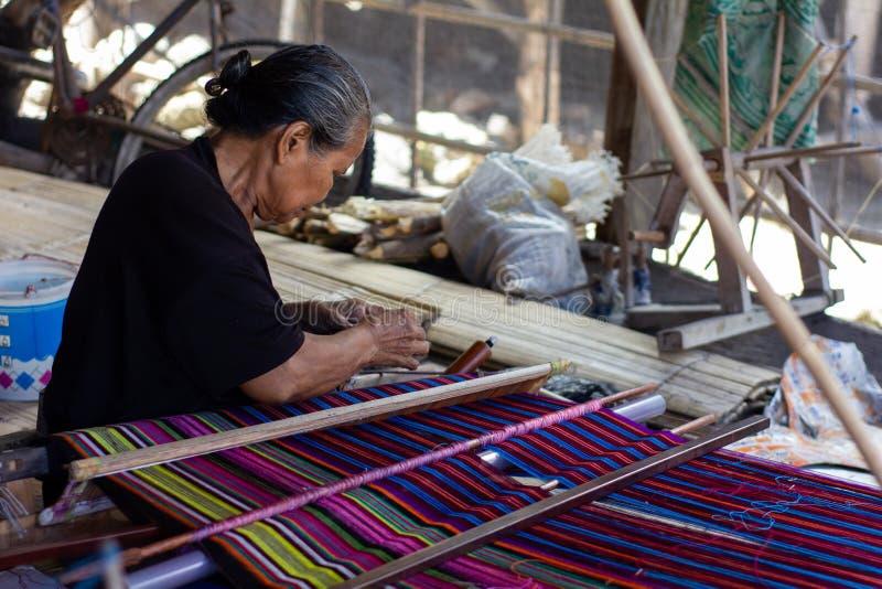 En kvinna väver traditionella färgrika tyger av Flores Alla väva processar använder manuell och traditionell utrustning arkivbild