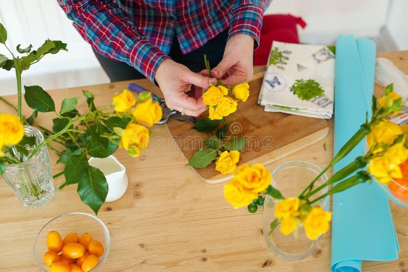 En kvinnablomsterhandlare gör en bukett På rosorna för tabelllögnblommor Flickan med sax klipper rosen royaltyfri fotografi