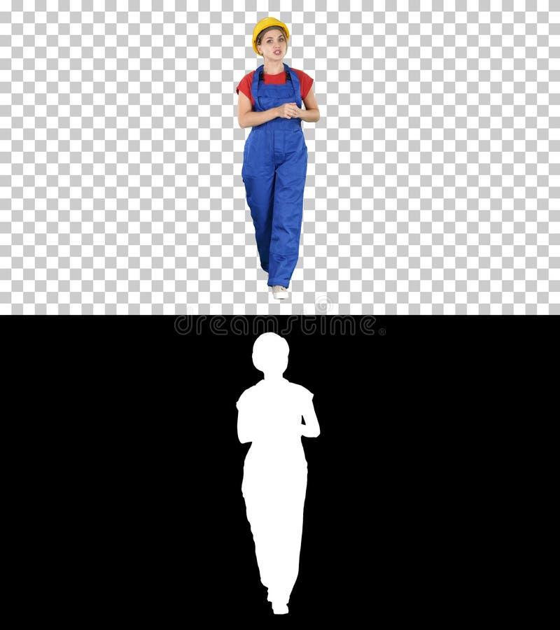 En kvinnabyggnadsarbetare som talar till kameran i s?ker v?g, Alpha Channel arkivfoto