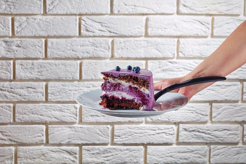 En kvinnahand som rymmer en del av kakan royaltyfri bild