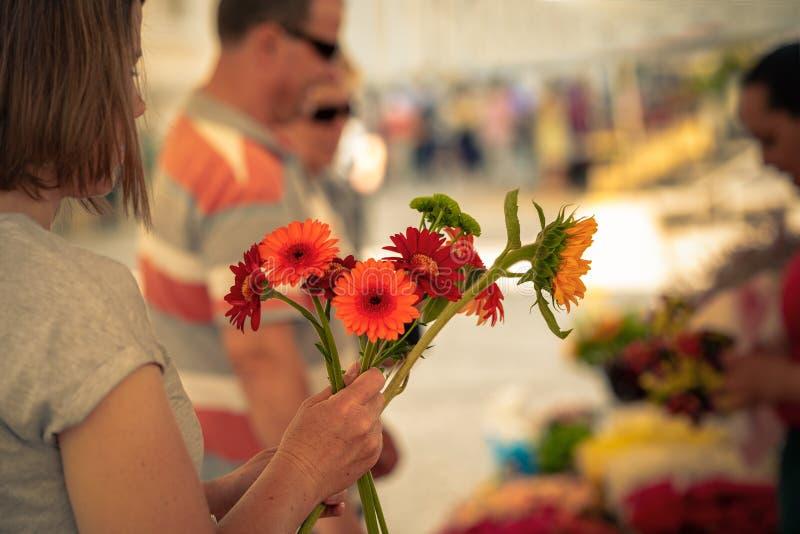 En kvinnakund gör en bukett av en gatasäljare av nya blommor, en blomsterhandlare arkivfoto