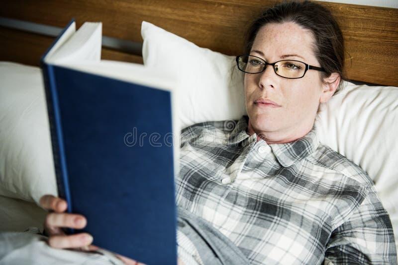En kvinnaläsning i säng royaltyfria bilder