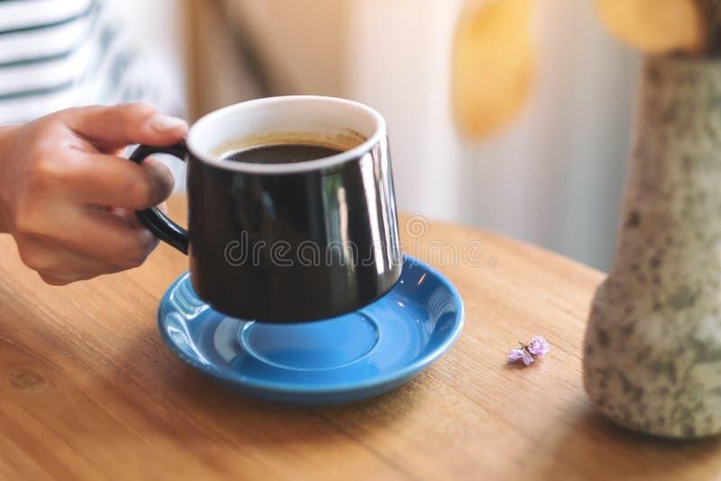 En kvinnas hand som rymmer en grön kopp av varmt kaffe på trätabellen royaltyfria bilder