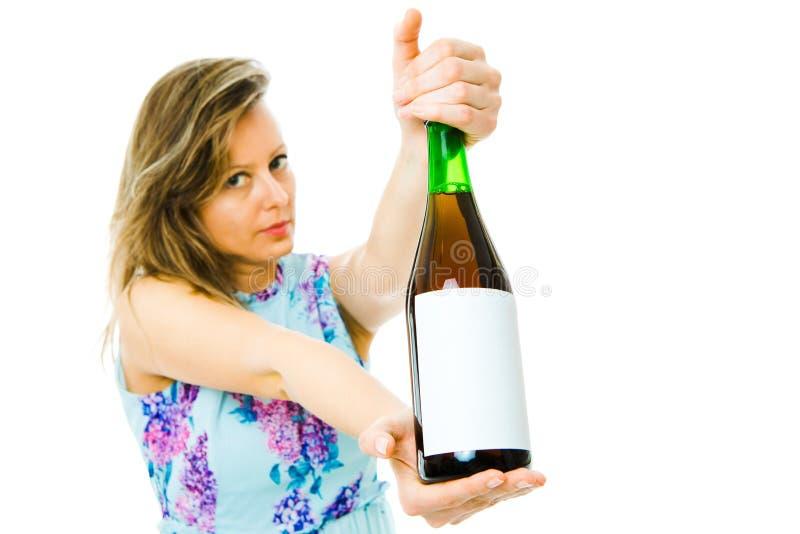 En kvinnavisningflaska av r?tt mousserande vin med tom etikett fotografering för bildbyråer