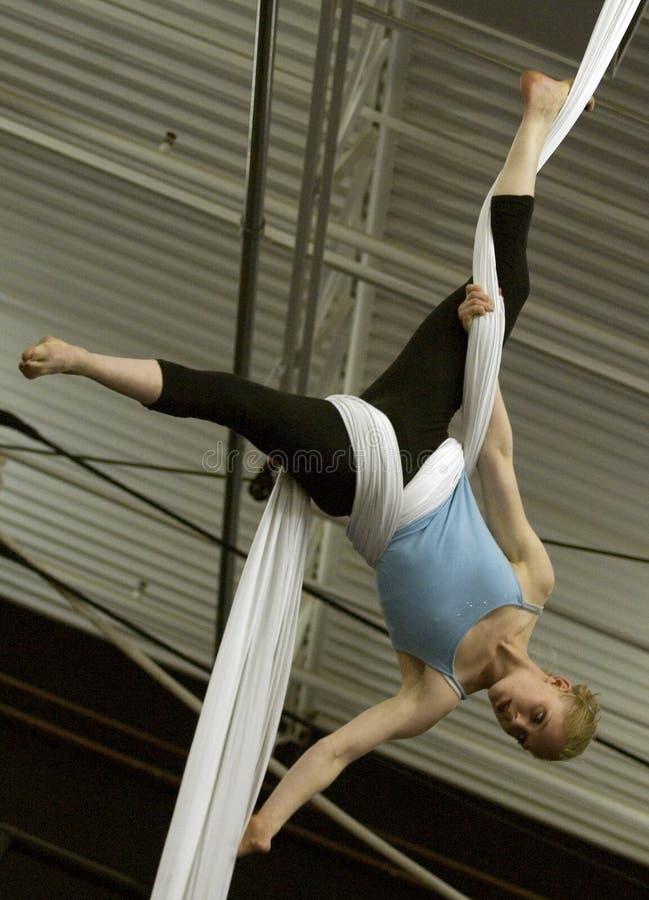 En kvinnlig akrobat hänger uppochnervänt, genom att slå in flyg- silke runt om hennes midja och ben arkivfoton