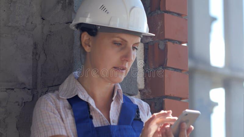 En kvinnlig arbetare för ung konstruktion sitter på en plats och arbetar på en smartphone royaltyfria bilder