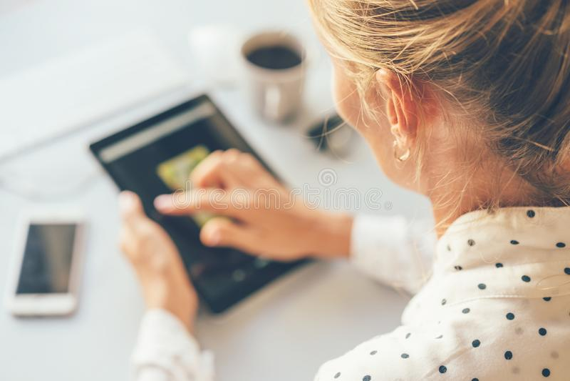 En kvinnlig blogger använder en pekskärm för att söka för information på internet arkivbilder