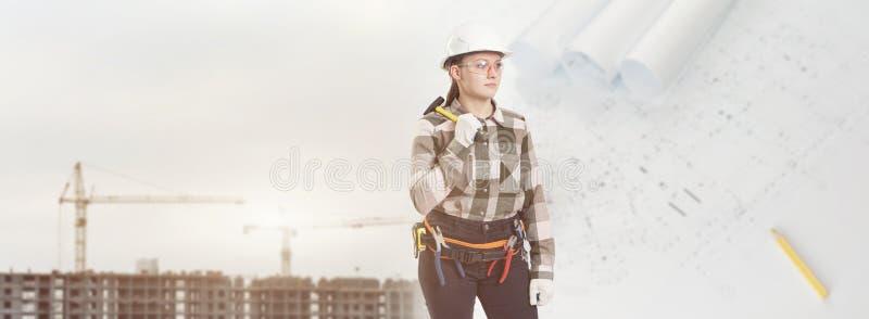 En kvinnlig byggnadsarbetare i säkerhetshjälm rymmer en hammare arkivfoton