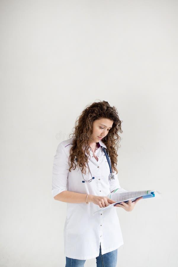 En kvinnlig doktor med en mapp som isoleras på vit bakgrund med kopieringsutrymme Vertikalt foto arkivfoto