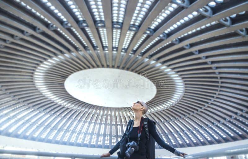 En kvinnlig fotograf som beundrar ett enormt runt konserthalltak arkivbilder