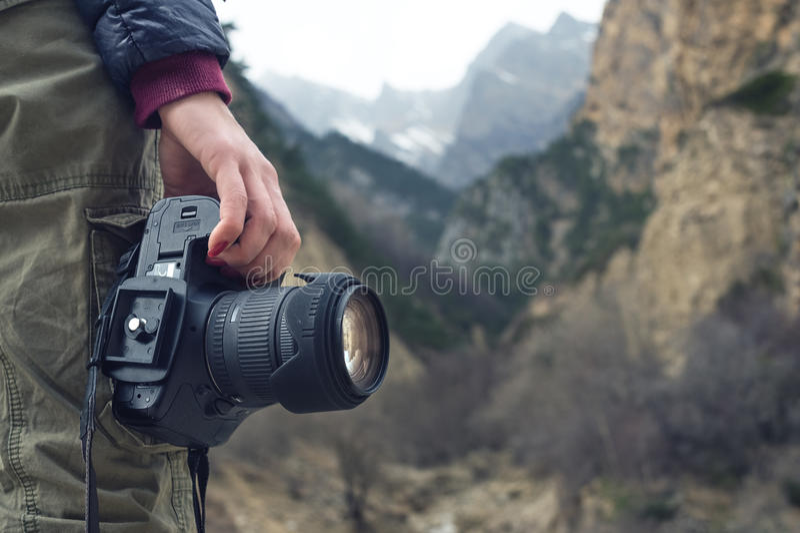 En kvinnlig hand rymmer en kamera mot ett berglandskap royaltyfria bilder