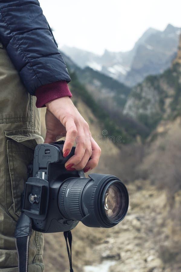 En kvinnlig hand rymmer en kamera mot ett berglandskap arkivbilder