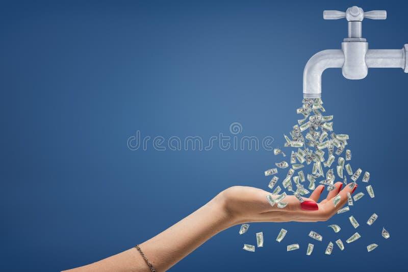 En kvinnlig hand rymmer hennes hand under en ström av pengar som flödar från ett metallklapp royaltyfria foton