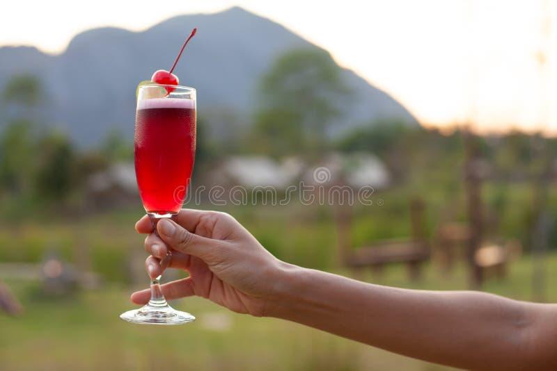 En kvinnlig hand som har ett högt exponeringsglas av den röda coctailen som dekoreras med den röda körsbäret med bergsikt royaltyfria bilder