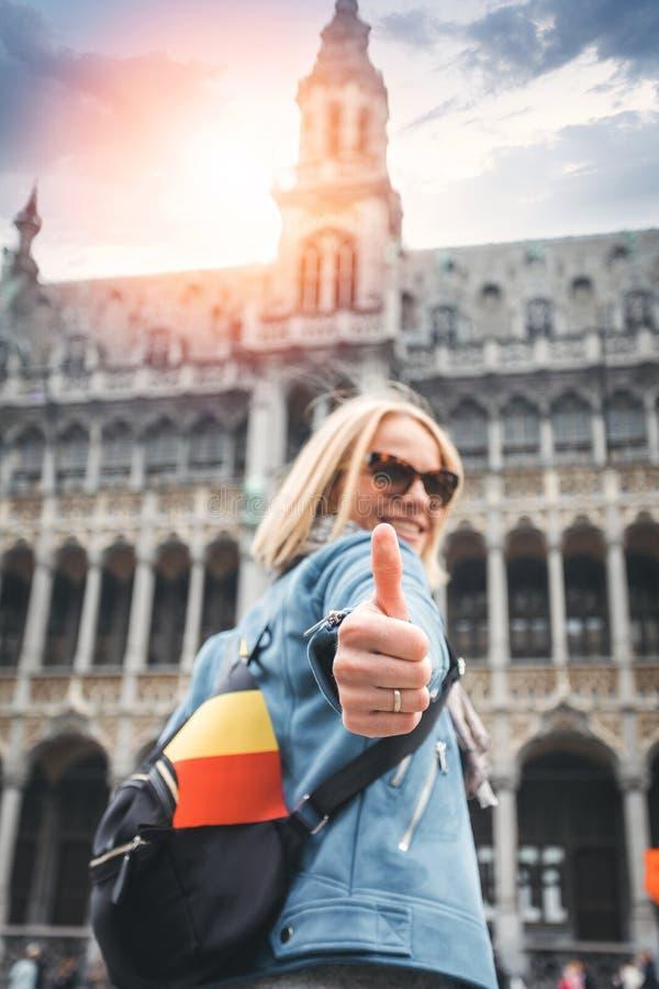 En kvinnlig handelsresande står på den Grand Place fyrkanten i Bryssel och visar upp hennes tummar, Belgien royaltyfria foton
