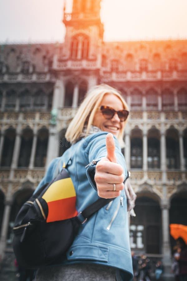 En kvinnlig handelsresande står på den Grand Place fyrkanten i Bryssel och visar upp hennes tummar, Belgien arkivfoton