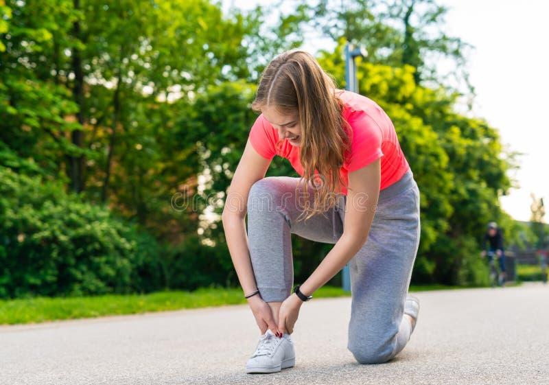 En kvinnlig jogger har sårat hennes fot och har smärtar royaltyfri bild
