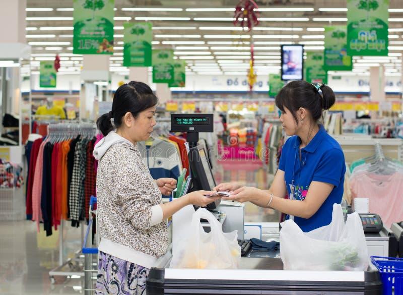 En kvinnlig kassörska av den Coopmart supermarket royaltyfria foton