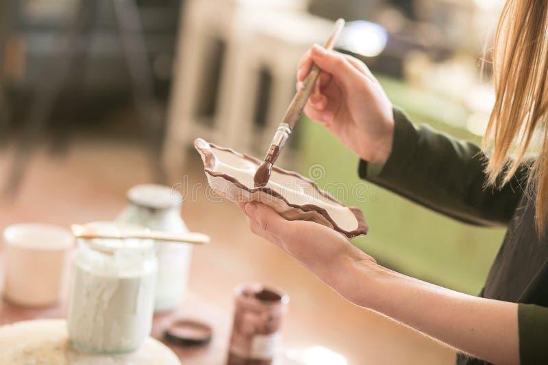 En kvinnlig konstnär av seminariet målar en platta keramik royaltyfri fotografi
