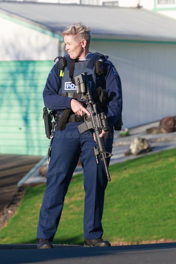 En kvinnlig medlem av den nyazeeländska polisen och beväpnat och bevaka en gata fotografering för bildbyråer