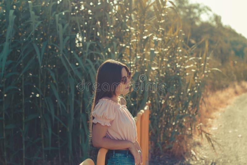 En kvinnlig modell i en utomhus- avkopplad väg i en solig sommardag arkivfoton