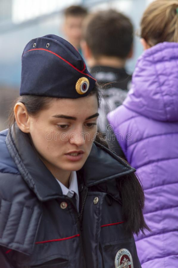 En kvinnlig polis ser försiktigt Besk?da framifr?n royaltyfri foto