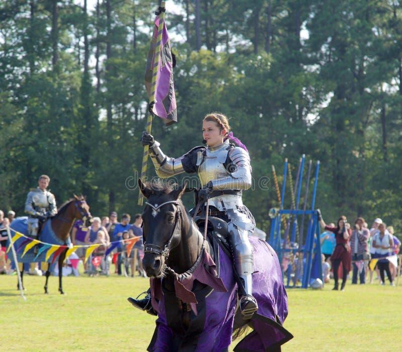 En kvinnlig riddare bär en flagga på en häst på densöder renässans Faire arkivbilder