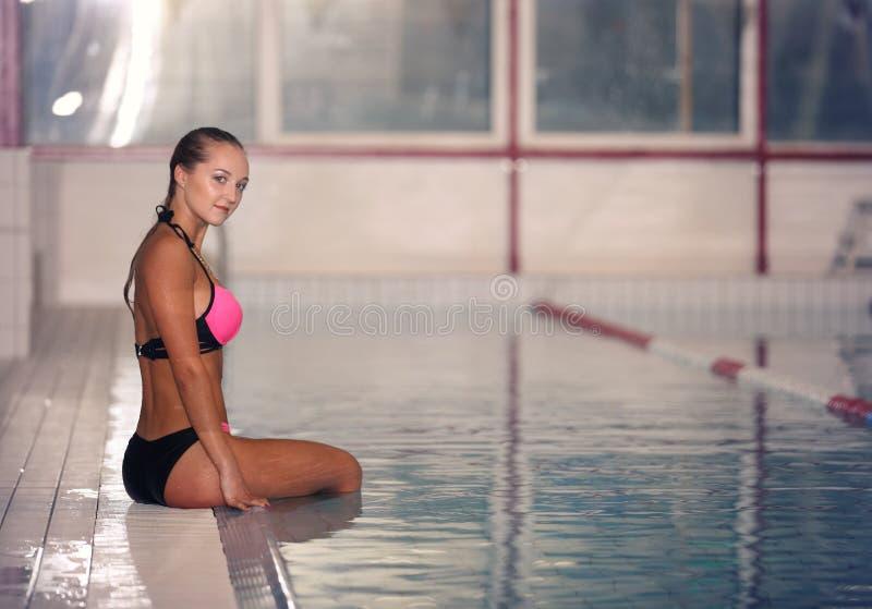 En kvinnlig simmare i simbassäng för inomhus sport flicka i rosa sweimsuitutbildning fotografering för bildbyråer