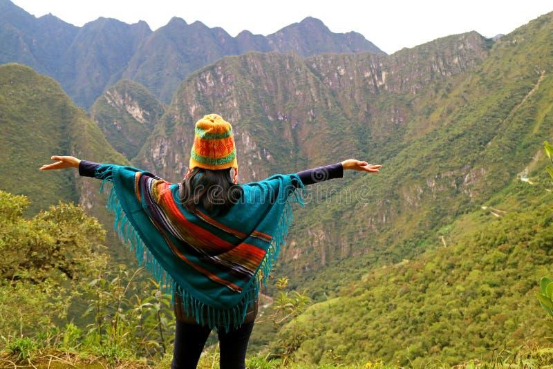 En kvinnlig som lyfter hennes armar på synvinkeln på det Huayna Picchu berget, Machu Picchu, Cusco region av Peru fotografering för bildbyråer
