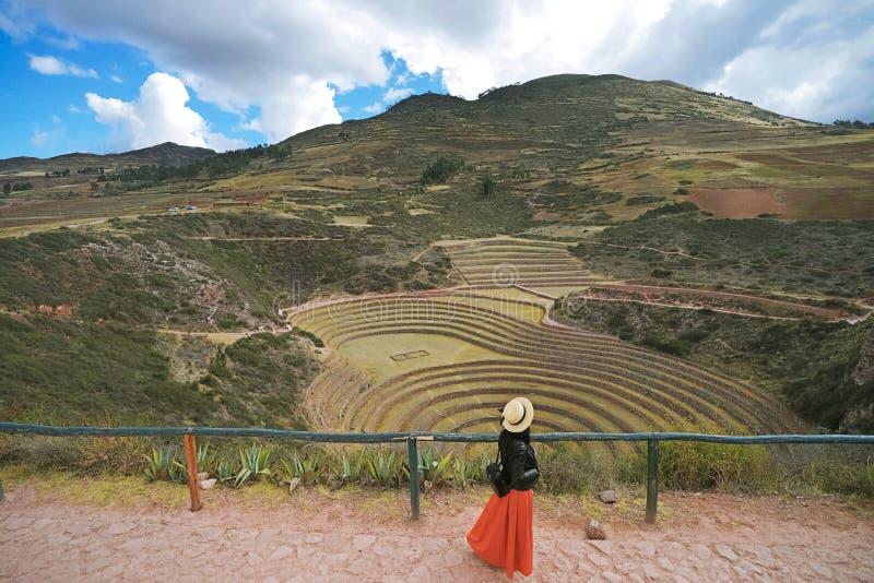 En kvinnlig turist, som bär ett svart omslag och en orange kjol, går på incaen fördärvar namngiven `-Moray`, Dess design skapar e royaltyfria bilder