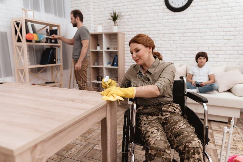 En kvinnlig veteran i en rullstol gör ren huset Henne ` s i militär likformig royaltyfria foton