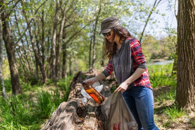 En kvinnlig volontär hjälper rent skogen av skräp Begrepp av ekologi och jorddagen royaltyfri bild