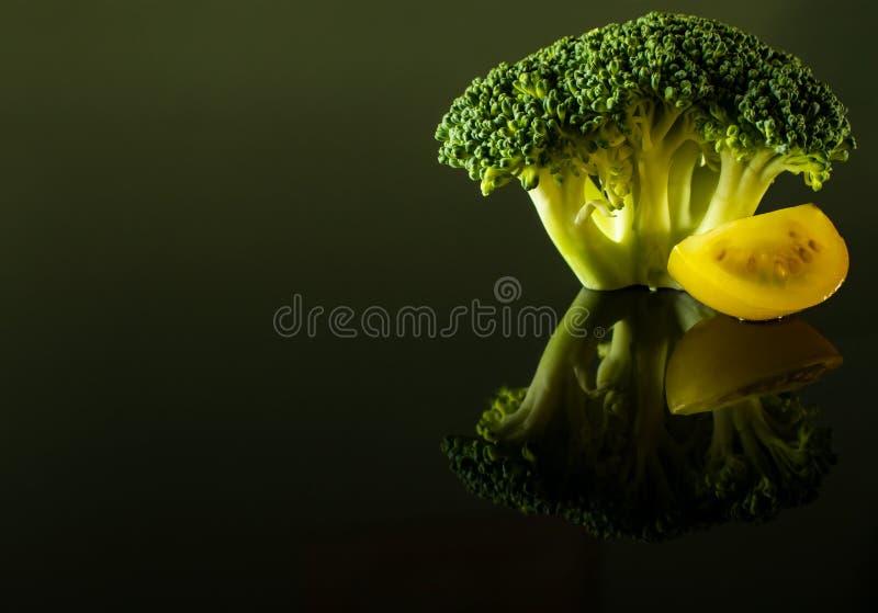 En kvist av broccoli med en skiva av den gula körsbärsröda tomaten royaltyfria bilder