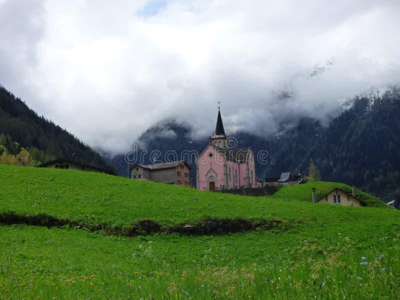 En kyrka i de schweiziska fjällängarna med dimma som hänger precis ovanför kyrktorn royaltyfri fotografi