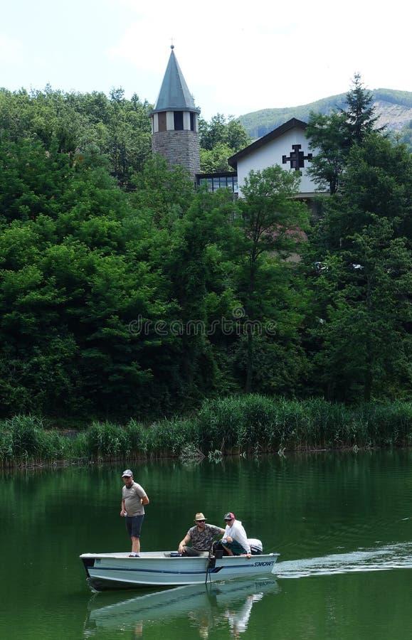 En kyrka med dess klockatorn och fartyg på sjön av Castel dell` Alpi royaltyfria foton