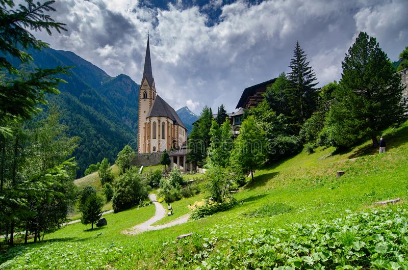 En kyrka sitter bland bergig terräng i Heiligenblut, Österrike arkivfoton