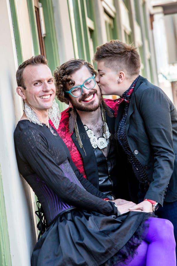 En kyss bland tre genusvätskevänner royaltyfri fotografi