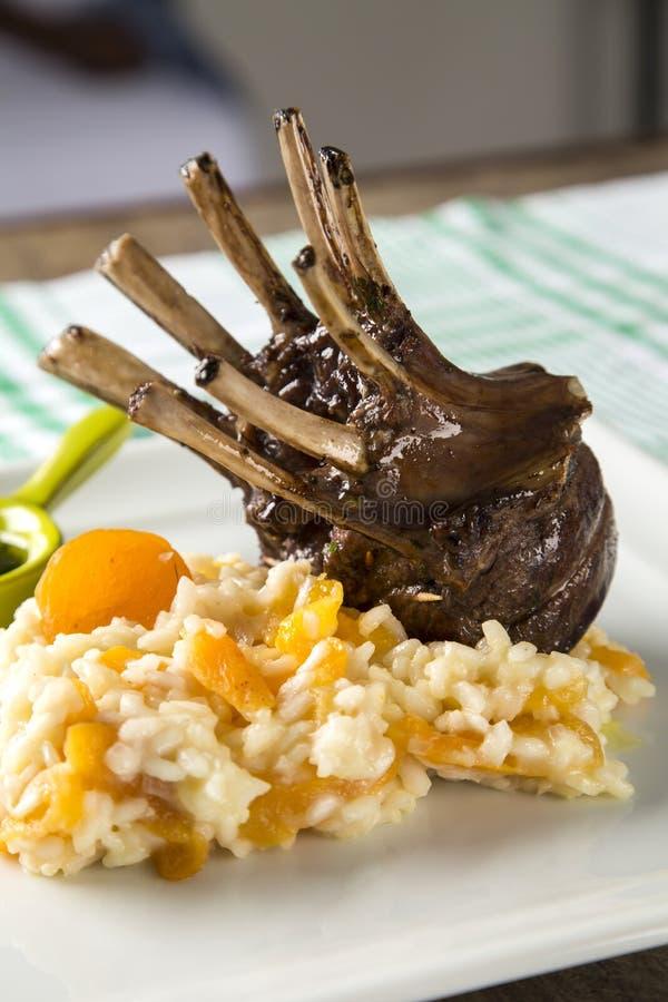En läcker maträtt av kuggen av lammet med ris och aprikons på en squa royaltyfria bilder