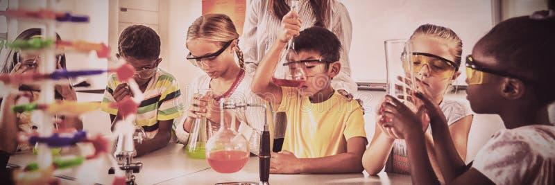 En lärare som poserar med elever som gör vetenskapsprojekt royaltyfri foto
