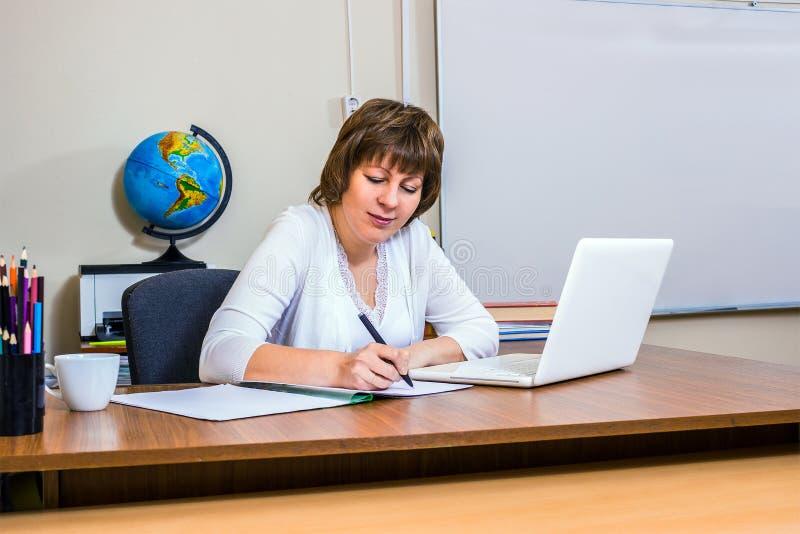 En lärarinna arbetar med en bärbar dator i klassrumet arkivbilder