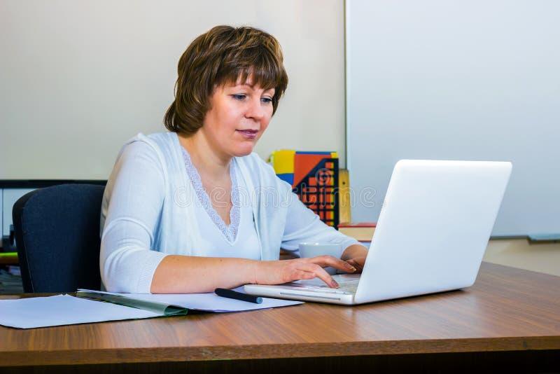 En lärarinna arbetar med en bärbar dator i klassrumet royaltyfri bild