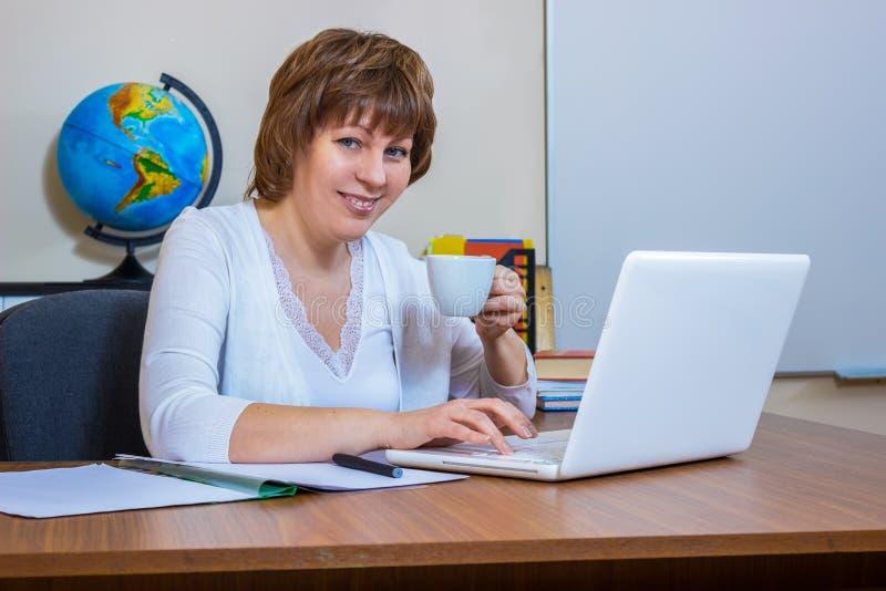 En lärarinna arbetar med en bärbar dator i klassrumet royaltyfri foto