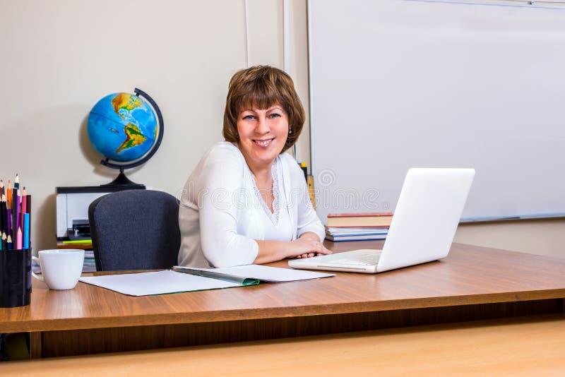 En lärarinna arbetar på en dator i klassrumet royaltyfri fotografi