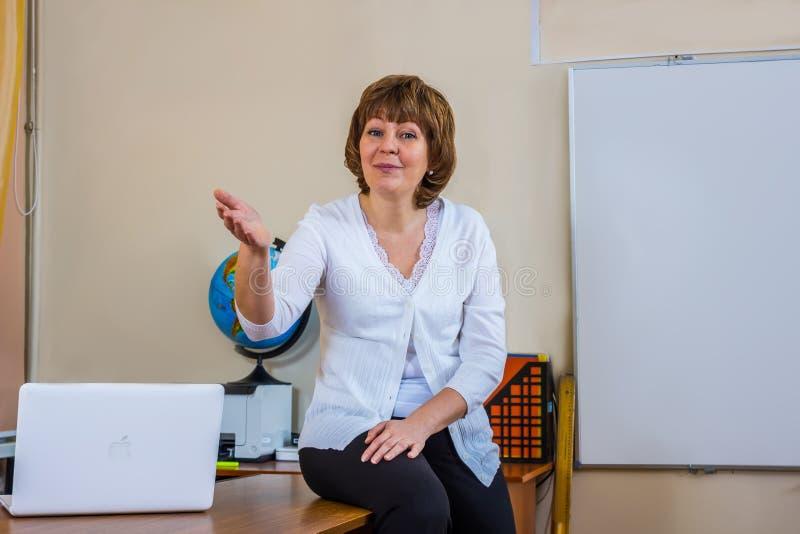 En lärarinna i ett klassrum rymmer en kurs arkivbilder