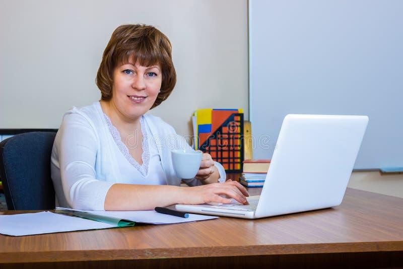 En lärarinna på en tabell i klassrumet arkivbilder