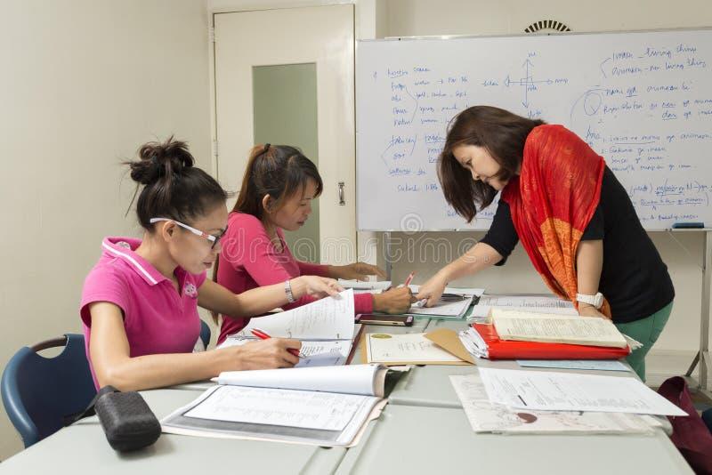 En lärarinna som undervisar två flickor i klassrum på skola royaltyfria foton