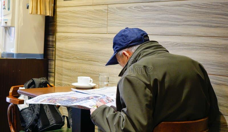 En läs- nyheterna för gamal man på coffee shop i Taipei arkivfoton