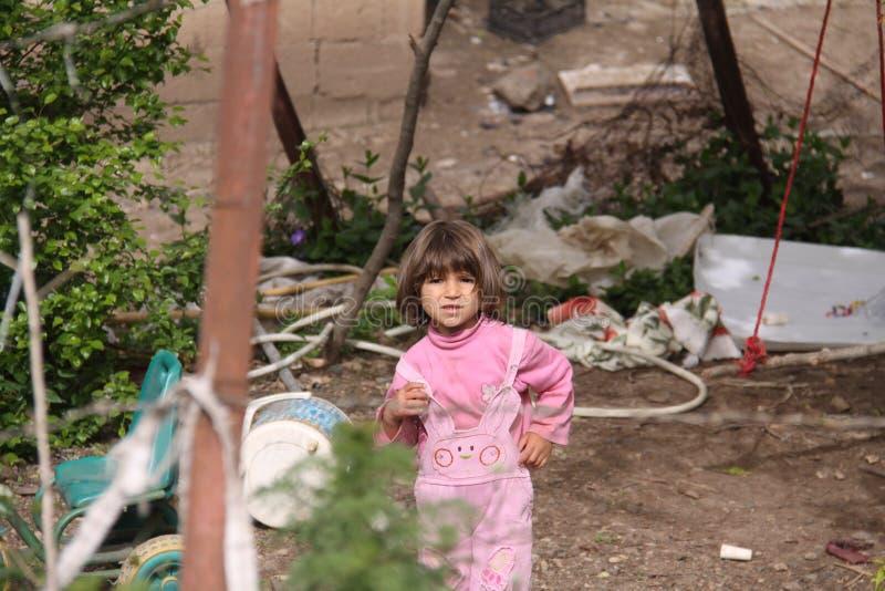 En läskig liten flicka utanför staden, en gunga, olik utrustning och växter är synliga i bakgrund, Iran, Gilan royaltyfri foto